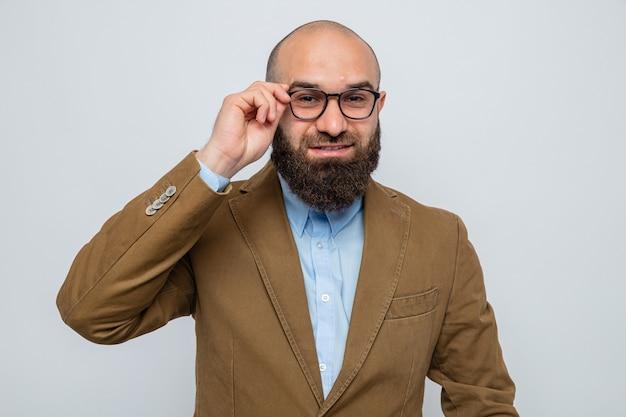 Uomo barbuto in abito marrone con gli occhiali che sembra sorridente allegramente toccando i suoi occhiali