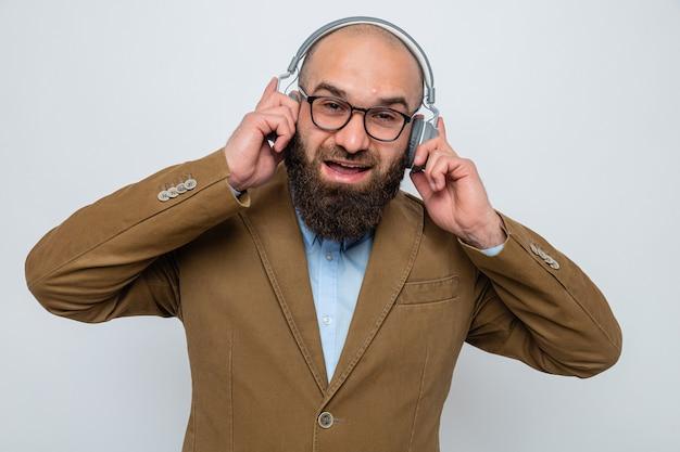 Uomo barbuto in abito marrone con gli occhiali con le cuffie che sorride allegramente godendosi la sua musica preferita