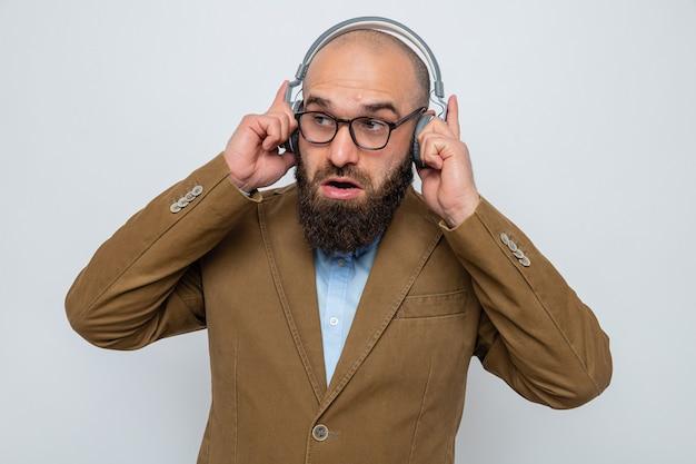 Uomo barbuto in abito marrone con gli occhiali con le cuffie che sembra sorpreso sorridente godendosi la sua musica preferita in piedi su sfondo bianco