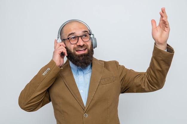 Uomo barbuto in abito marrone con gli occhiali con le cuffie guardando in alto sorridendo felice ed eccitato godendo la sua musica preferita in piedi su sfondo bianco