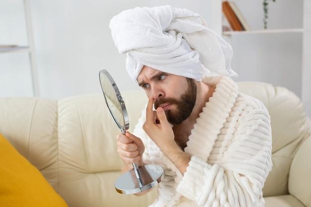 Uomo barbuto che controlla la pelle del viso. spa, cura del corpo e della pelle per il concetto maschile.