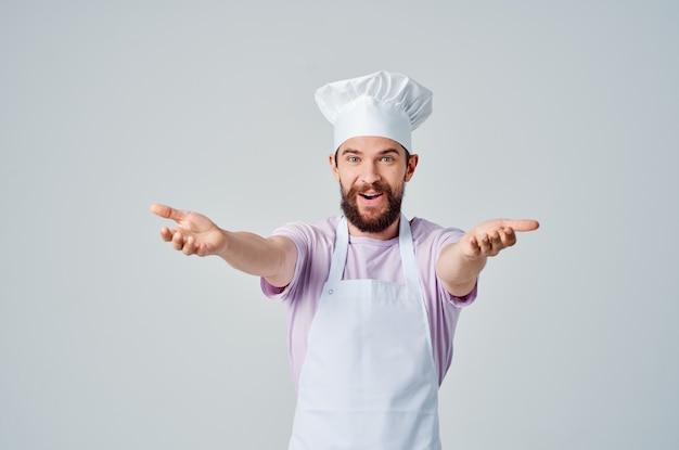 Un uomo barbuto in divisa da chef gesticola con le mani le emozioni dei professionisti. foto di alta qualità