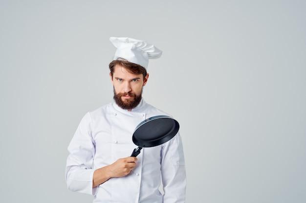 Lo chef uomo barbuto con una padella in mano ha isolato lo sfondo