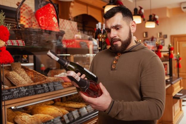 Uomo barbuto che sceglie tra due bottiglie ow champagne, shopping per la celebrazione delle vacanze, copia dello spazio