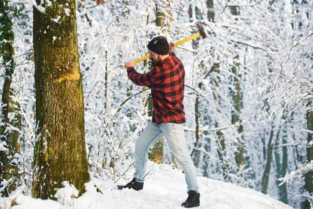 Uomo barbuto che taglia un albero a pezzi. boscaiolo barbuto. boscaiolo barbuto brutale con l'ascia nella foresta invernale. bell'uomo, hipster nella foresta innevata. boscaiolo con un'ascia in mano.