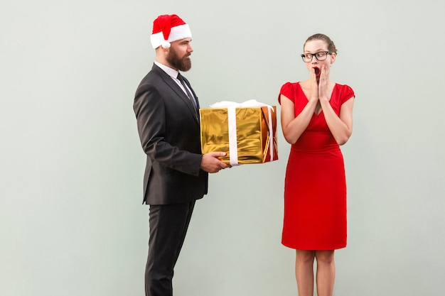 L'uomo barbuto con il cappello di natale regala una bella donna in abito rosso con la faccia scioccata