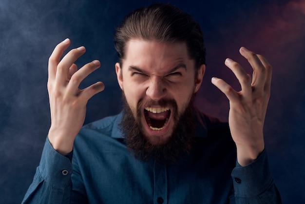 Uomo barbuto sigarette vape in posa primo piano di emozioni. foto di alta qualità