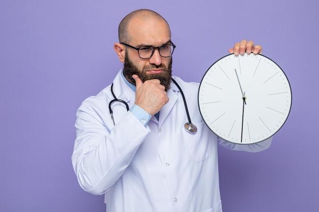 Medico uomo barbuto in camice bianco con stetoscopio intorno al collo che tiene l'orologio che guarda da parte con espressione pensierosa in piedi su sfondo viola