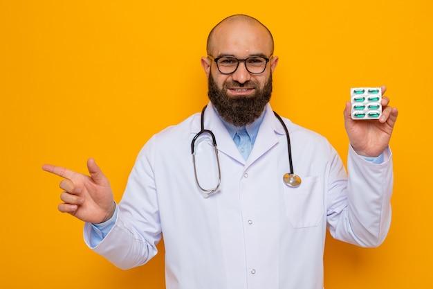 Uomo barbuto medico in camice bianco con uno stetoscopio intorno al collo con gli occhiali che tiene blister con pillole felice e positivo che punta con il dito indice a lato