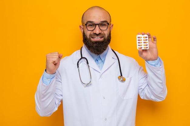 Uomo barbuto medico in camice bianco con stetoscopio intorno al collo con gli occhiali che tengono blister con pillole guardando la telecamera felice ed eccitato in piedi su sfondo arancione