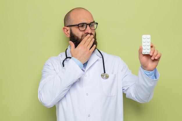 Uomo barbuto medico in camice bianco con stetoscopio intorno al collo con gli occhiali che tengono blister con pillole guardandolo scioccato che copre la bocca con la mano