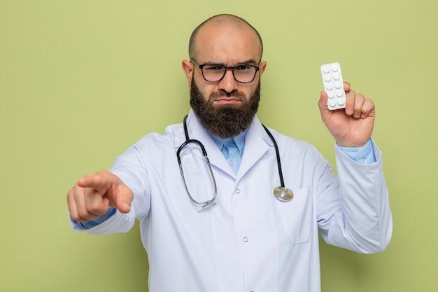 Uomo barbuto medico in camice bianco con stetoscopio intorno al collo con gli occhiali che tengono blister con pillole puntate con il dito indice davanti