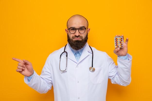 Uomo barbuto medico in camice bianco con stetoscopio intorno al collo con gli occhiali che tengono blister con pillole che puntano con il dito indice al lato sorridente in piedi su sfondo arancione