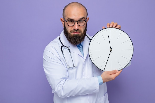 Medico uomo barbuto in camice bianco con stetoscopio intorno al collo con gli occhiali che tengono l'orologio guardando con faccia seria