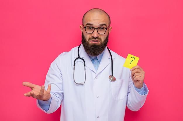 Uomo barbuto medico in camice bianco con uno stetoscopio intorno al collo con gli occhiali tenendo la carta di promemoria con un punto interrogativo confuso alzando il braccio con dispiacere