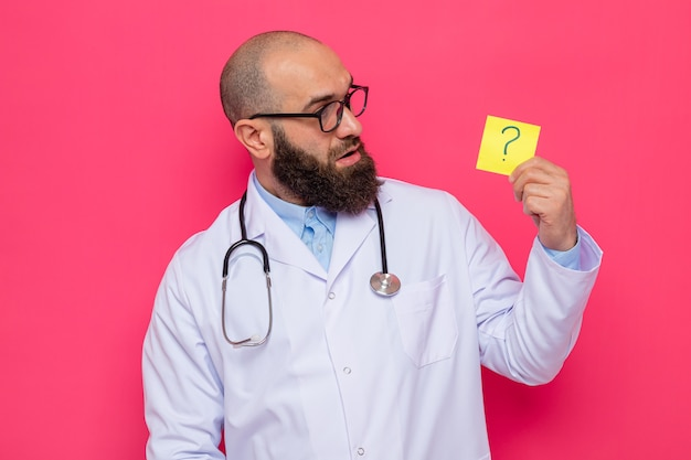 Medico uomo barbuto in camice bianco con stetoscopio intorno al collo con gli occhiali che tengono carta promemoria con punto interrogativo guardandolo sorpreso in piedi su sfondo rosa