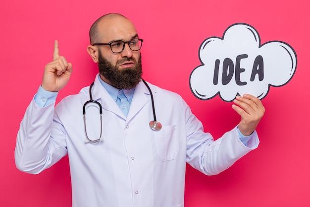 Uomo barbuto medico in camice bianco con uno stetoscopio intorno al collo con gli occhiali tenendo il segno del fumetto con idea di parola che osserva da parte con la faccia seria che mostra il dito indice