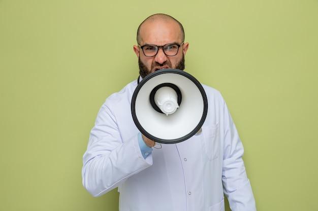 Medico uomo barbuto in camice bianco con stetoscopio intorno al collo con gli occhiali che grida al megafono con espressione aggressiva