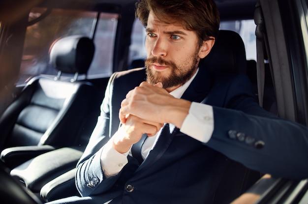 Uomo barbuto che guida un servizio di successo di stile di vita di lusso di viaggio in auto ricco