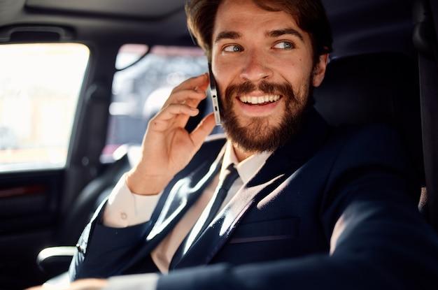 Uomo barbuto che guida un servizio di successo di stile di vita di lusso in viaggio in auto ricco