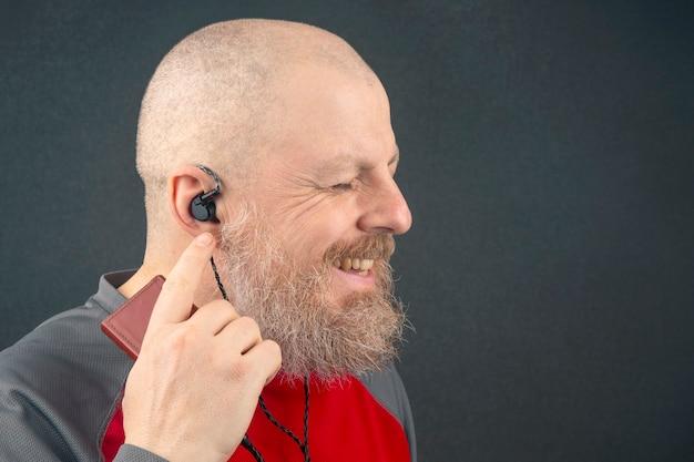 L'uomo barbuto si diverte ad ascoltare la sua musica preferita attraverso un lettore audio in piccole cuffie. audiofilo e amante della musica. musica e suono hi-fi.