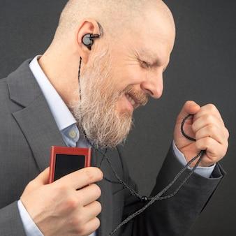 L'uomo barbuto gode di ascoltare la sua musica preferita attraverso un lettore audio in piccole cuffie.