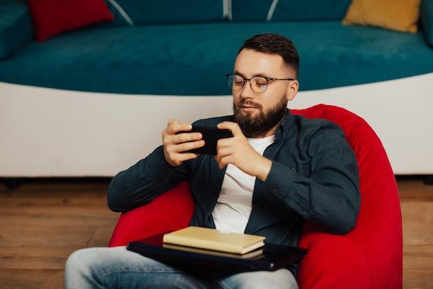 L'uomo barbuto in occhiali da vista si siede sulla poltrona rossa e si rilassa a casa mentre si utilizza il moderno telefono cellulare dopo il lavoro al notebook.