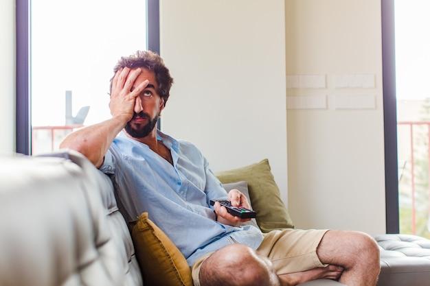 Uomo barbuto che si sente annoiato, frustrato e assonnato dopo un compito noioso, noioso e noioso, tenendo la faccia con la mano