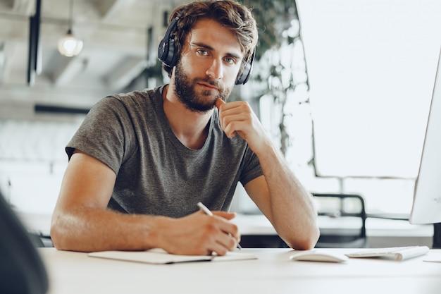 Lavoratore indipendente barbuto che fa le note in suo blocco note. concetto di pianificazione