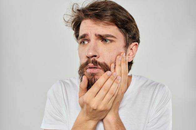 Uomo barbuto che gesturing con lo stile di vita di studio della maglietta tagliata bianca della mano