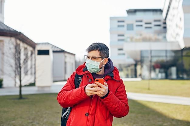 Uomo barbuto con occhiali e maschera protettiva che cammina per la strada moderna con il telefono e guarda al lato, maschio solo all'aperto in protezione respiratoria per evitare covid19