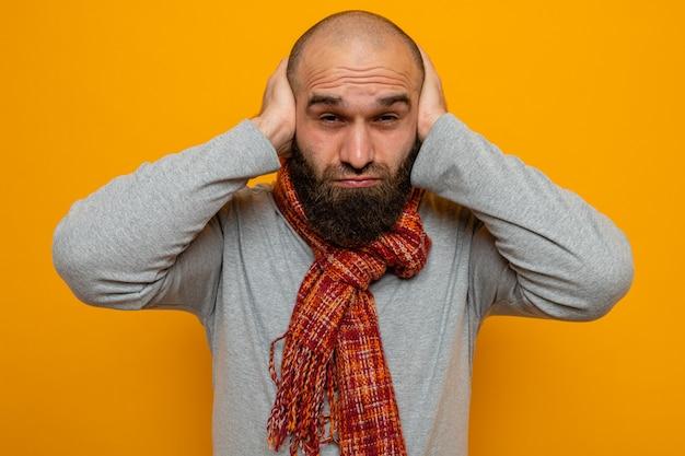Uomo barbuto in felpa grigia con sciarpa intorno al collo che guarda la telecamera confusa con le mani sulla testa in piedi su sfondo arancione