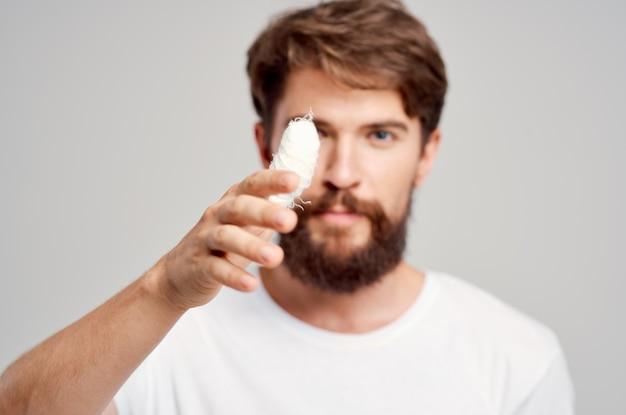 Uomo barbuto infortunio alla mano trattamento problemi di salute emozioni sfondo chiaro