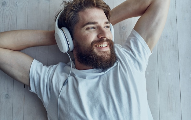 Uomo barbuto in cuffie che ascolta la musica per il tempo libero interior lifestyle