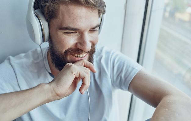 Uomo barbuto in cuffie che ascolta la musica vicino al divertimento della finestra. foto di alta qualità