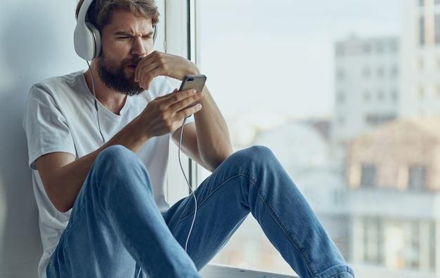 Uomo barbuto in cuffie che ascolta la musica vicino alla tecnologia di ricreazione della finestra
