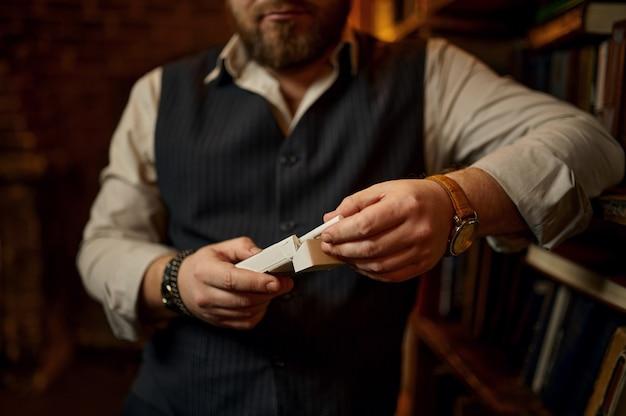 L'uomo barbuto tiene un pacchetto di sigarette, una libreria e un ricco interno di ufficio sullo sfondo. cultura del fumo di tabacco, sapore specifico. abitudine al fumo