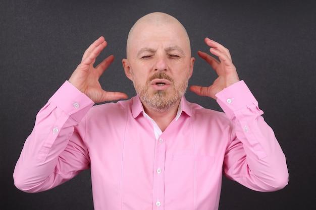 L'uomo barbuto è molto emotivamente stressato tenendo le mani vicino alla testa