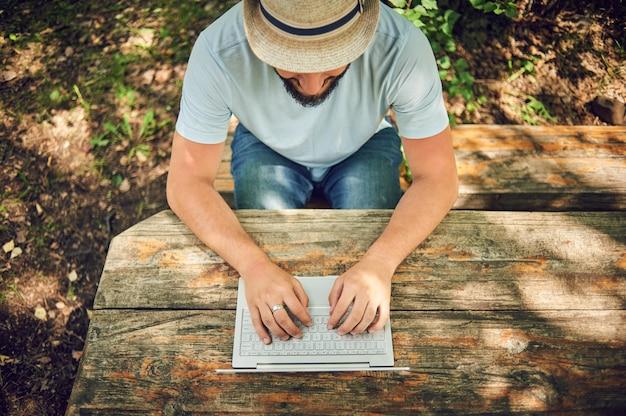 L'uomo barbuto sta lavorando e sorridendo con il computer portatile al parco sotto l'albero. felice libero professionista è seduto e utilizzando app o sito web sull'erba. lavora in remoto in modalità autoisolamento