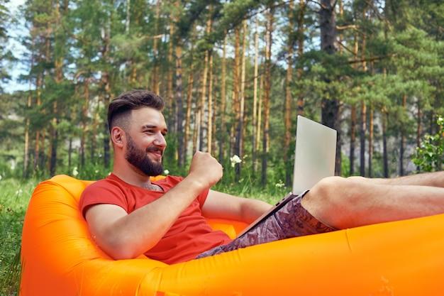 L'uomo barbuto sta lavorando e sorridendo con il computer portatile al parco sotto l'albero. felice libero professionista è seduto e utilizzando app o sito web sull'erba. lavora in remoto