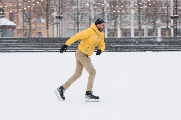 Uomo barbuto in giacca sulla pista di pattinaggio su ghiaccio in una giornata invernale nevosa
