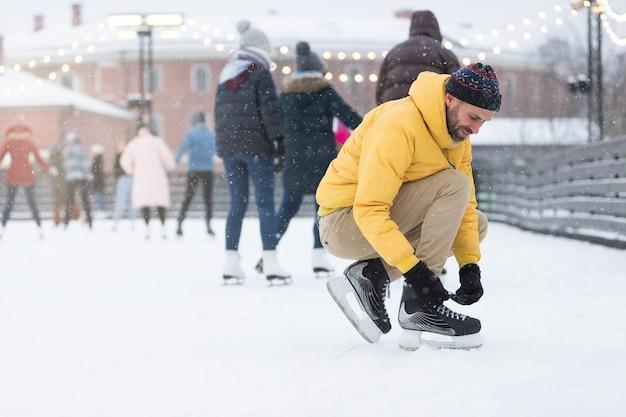 Uomo barbuto in giacca che lega i lacci delle scarpe sulla pista di pattinaggio su ghiaccio nel giorno di inverno nevoso