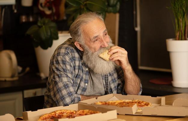 Uomo barbuto in una cucina. un uomo anziano in una camicia blu. maschio a casa con la pizza.