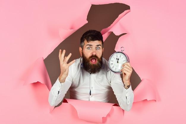Uomo barbuto che guarda attraverso il foro in carta rosa e tiene il concetto di affari di scadenza di tempo di risparmio dell'orologio