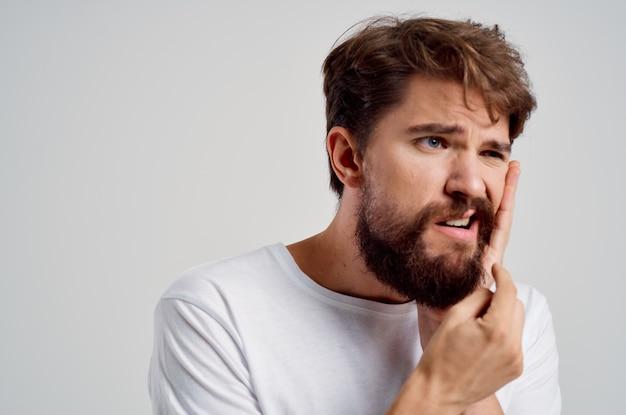 Uomo barbuto medicina mal di denti e problemi di salute sfondo chiaro