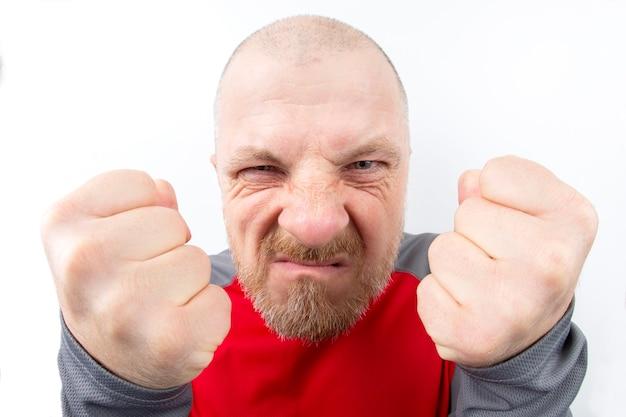 Uomo barbuto di sguardo minaccioso con il primo piano di pugni serrati su bianco