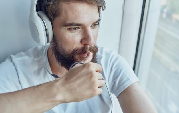 Uomo barbuto vicino alla finestra a casa con interni di tecnologia internet del telefono. foto di alta qualità