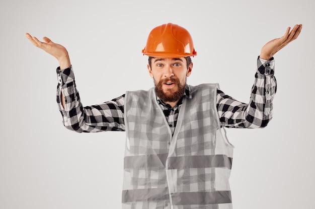 Uomo barbuto in arancione elmetto costruzione professionale sfondo isolato. foto di alta qualità