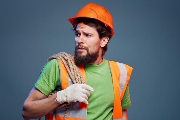 Il casco arancione dell'uomo barbuto sull'industria della testa ha isolato lo sfondo