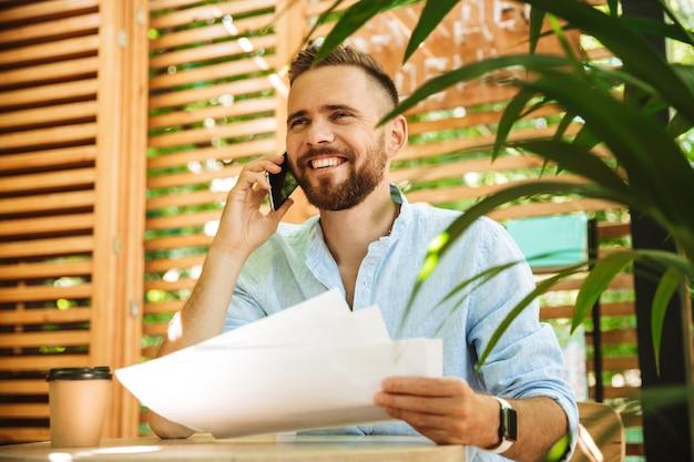 Uomo barbuto all'aperto parlando al telefono cellulare in possesso di documenti.